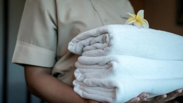 観光旅行の準備ができている高級ホテルの部屋のためのホテルメイドの手にタオル。