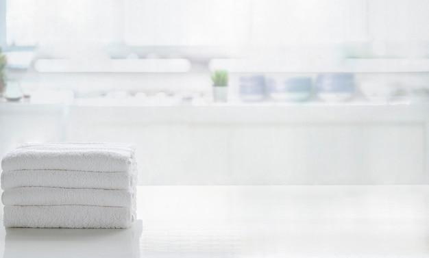 ぼやけキッチンルームにコピースペースを持つ白いトップテーブルにタオル。製品表示モンタージュ用。