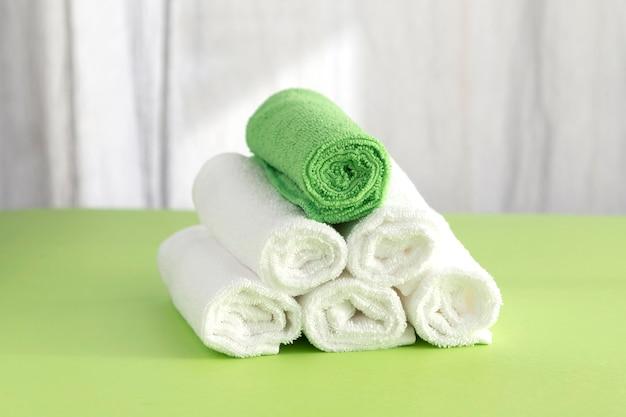 수건은 5 개의 흰색과 1 개의 녹색으로 롤러에 말려 피라미드로 접혔습니다. 스파 개념. 청결의 개념.