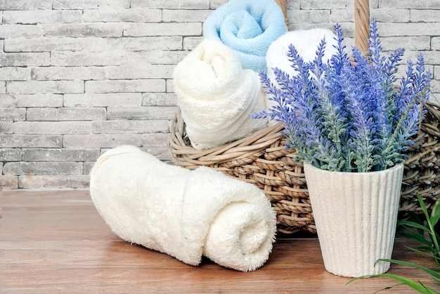 Towels rolls and houseplant on wooden table with old brick wall background.
