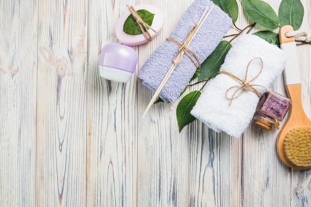 Towels; scrub bottle; moisturizing cream; leaves; brush and soap on wooden plank
