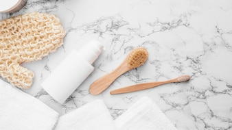 Towels; scrub glove; brush and cosmetic bottle on marble background