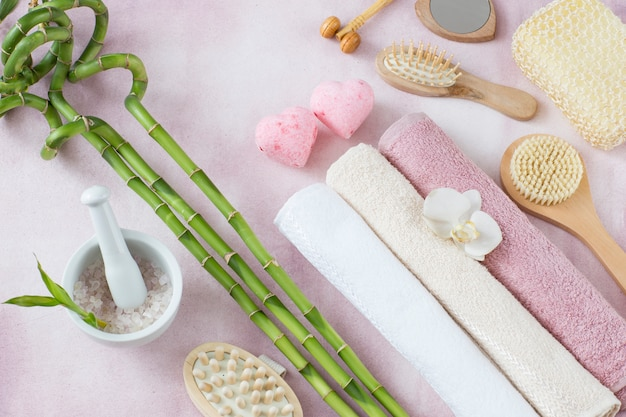 Towels, sea salt, bamboo and soap in the form of two pink hearts
