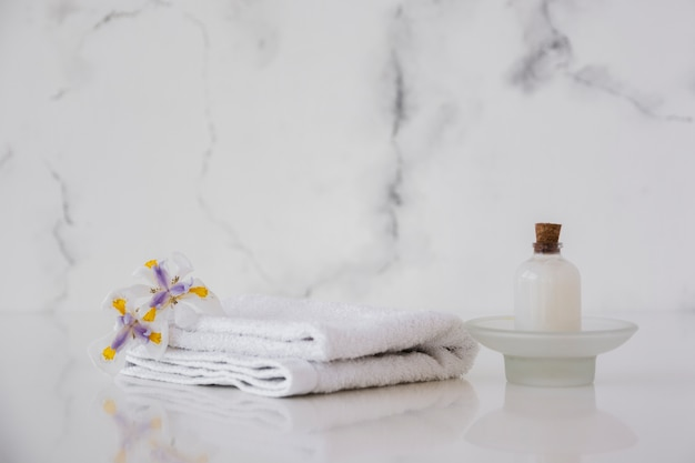 Towels and shower gel on table with marble background and copy space