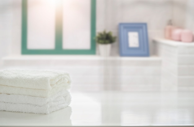 Towels on white table in bathroom with copy space.