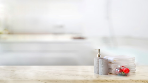Towels with ceramics shampoo and soap bottle on marble counter and copy space