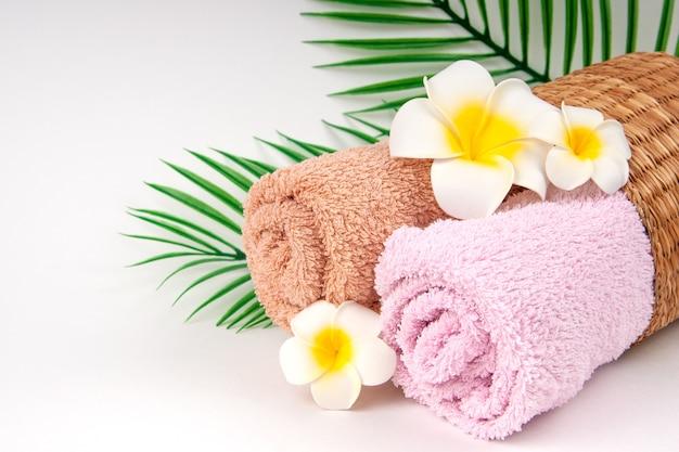プルメリアの花と熱帯のヤシの葉のコピースペース付きタオル。スキンケアとスパのコンセプト。
