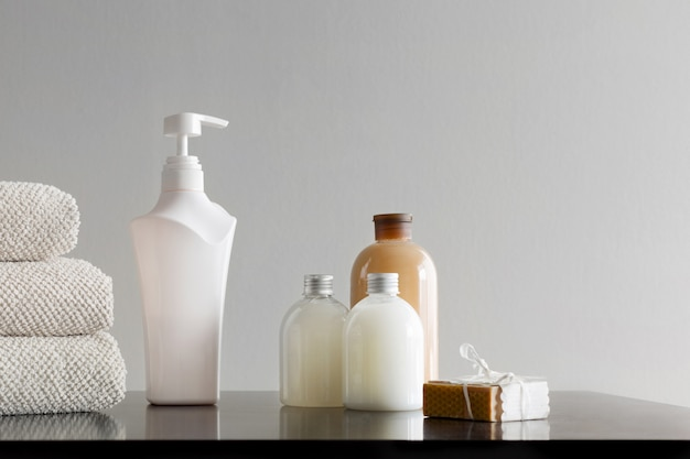 Towels with shampoo, body lotion, shower milk and handmade soap on neutral background.