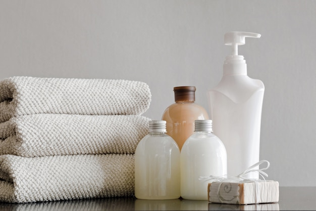 Towels with shampoo, conditioner, shower milk and handmade soap on neutral