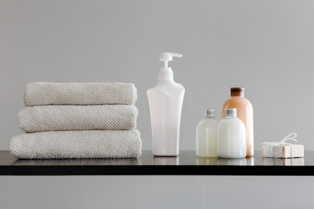 Towels with shampoo, conditioner, shower milk and handmade soap