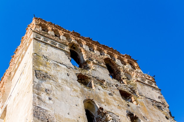 The tower of an ancient medieval castle on the background of a blue sky