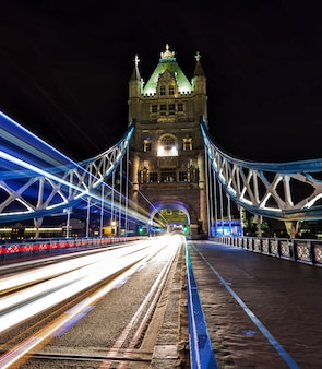 Tower bridge at night with bus and cars trails on the road