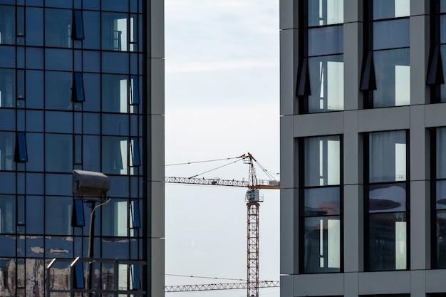 コンクリートとガラスの超高層ビルを備えた近代的な高層ビルの間のタワー建設クレーン