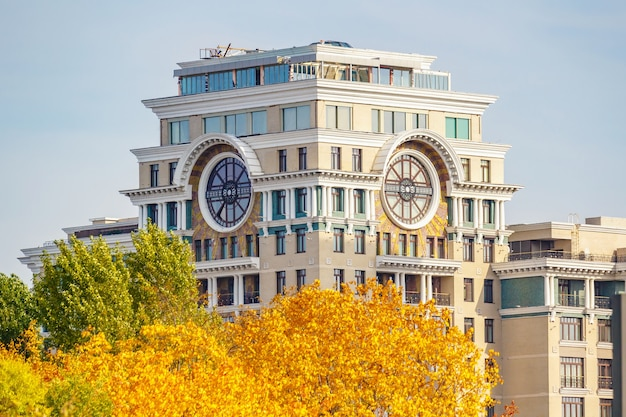 Tower of contemporary residential building against autumn trees with colored leaves