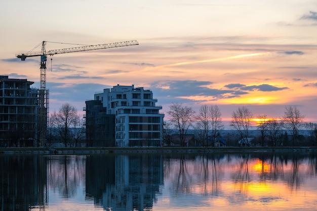 Строящийся башенный кран и высокие жилые дома на берегу озера