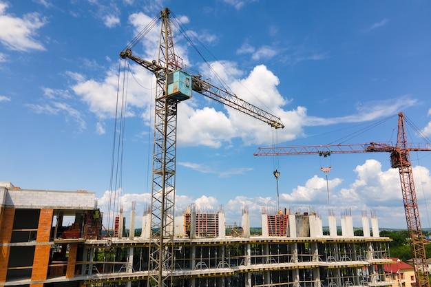 건설 중인 높은 콘크리트 주거용 건물에 있는 타워 크레인. 부동산 개발 개념입니다.