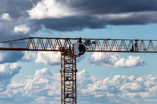 Tower crane close-up against the background of the cloudy sky. shooting from a drone. modern building technologies.