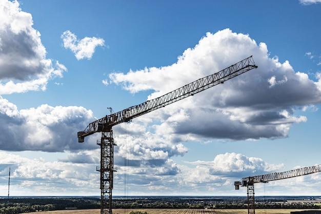 曇り空を背景にしたタワークレーンのクローズアップ。ドローンからの射撃。現代の建築技術。