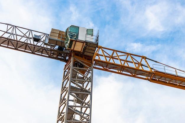 푸른 하늘 배경에 타워 크레인 클로즈업. 현대 주택 건설입니다. 산업 공학. 모기지 주택 건설.