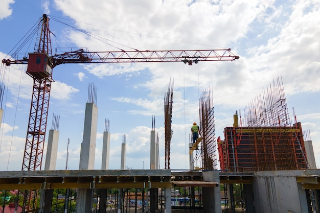 Tower crane at high concrete residential building under construction. real estate development concept.