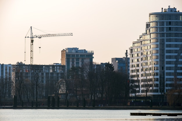 Tower crane and high residential apartment buildings under construction on lake shore. real estate development.