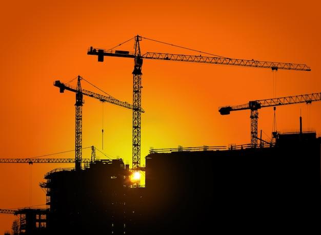 タワークレーンと日の出の労働者との建物のシルエット