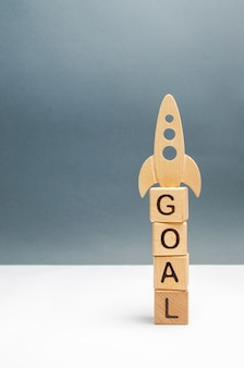 Tower of cubes with the word goal and rocket