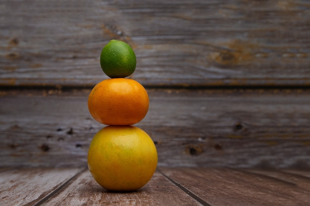 オレンジ、みかん、レモンと木製の背景で形成された塔