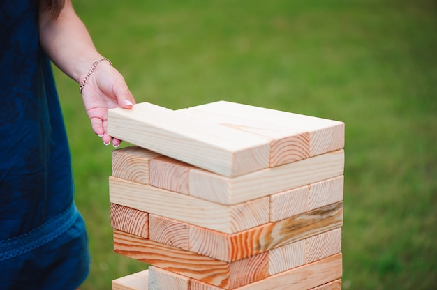 The tower from wooden blocks and man's hand take one block.