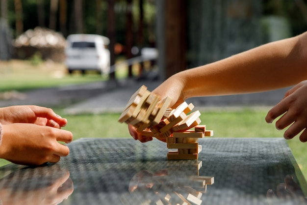 The tower from wooden blocks and woman hand take one block