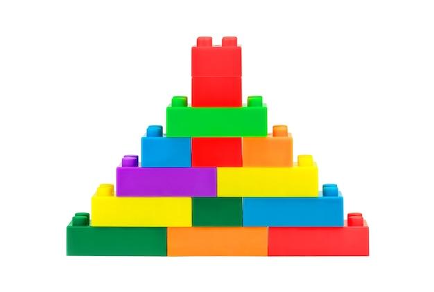 白い背景の上のプラスチックのおもちゃのブロックから作られた塔