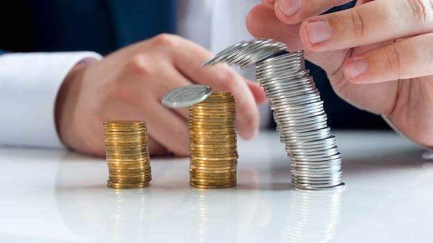 사무실 책상에 떨어지는 동전 타워에 의하여 이루어져있다. 글로벌 금융 위기와 파산의 개념.