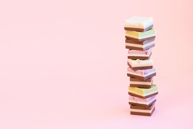 Башня из маленьких кусочков сладкого торта на розовом