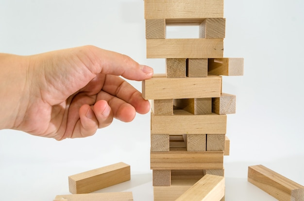 A tower made of wooden blocks and a mans hand takes one block risk concept