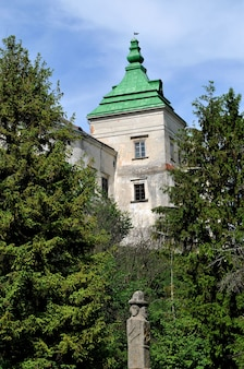 The tower of a medieval house in the middle of green trees