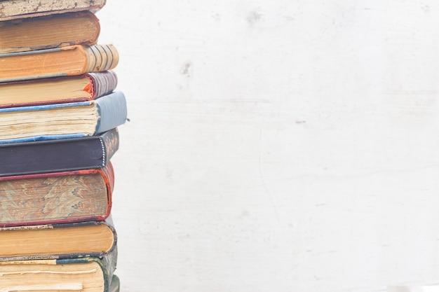 Башня книг крупным планом на белом деревянном