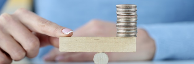 Башня монет на деревянном блоке и палец на другой стороне инвестиционной и торговой концепции