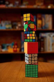 탁자 위에 있는 다채로운 퍼즐 큐브의 탑, 클로즈업 보기, 아무도 없습니다. 두뇌 및 논리적 마인드 훈련, 창의적인 게임, 복잡한 문제 해결을 위한 장난감