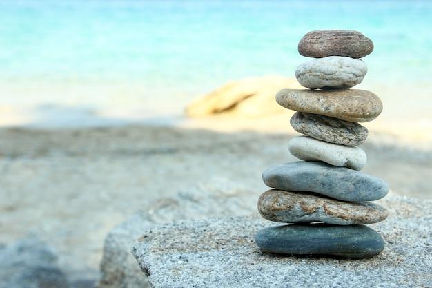 Башня из камней на песке на пляже