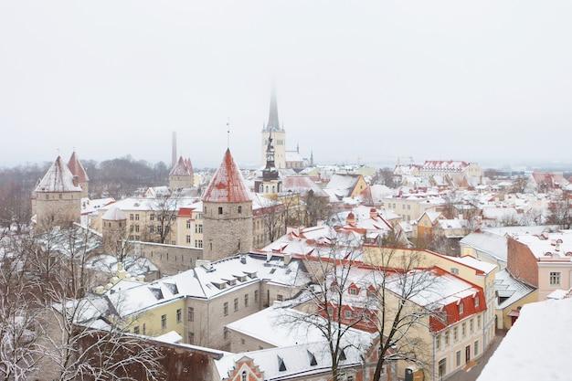 겨울철에 에스토니아의 탈린 구시가에 있는 성벽과 올레비스테 가톨릭 교회의 탑. 중세 매력적인 도시 탈린 구시가지와 눈의 고딕 스칸디나비아 건축.