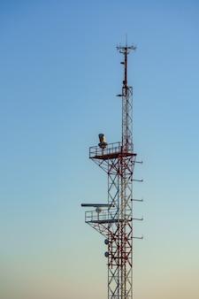 빨간색과 흰색 항공 안전 색상으로 칠해진 타워와 푸른 하늘에 대한 해상 레이더