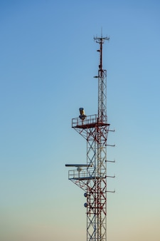 Tower painted in red and white aeronautical safety colors and a nautical radar against blue sky
