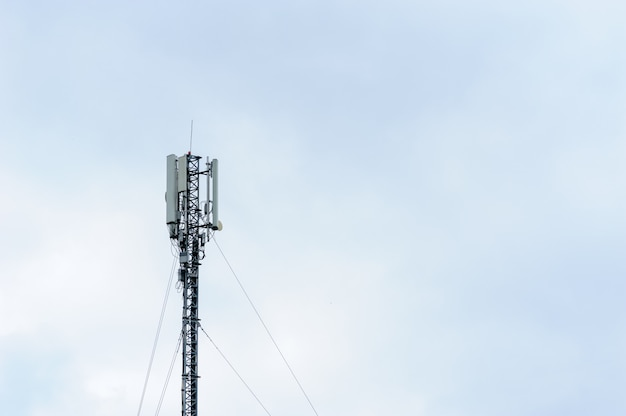 Tower with mobile operator antennas on the background of sky