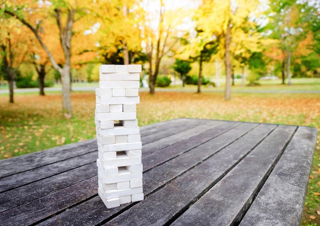 Tower of wooden block stack game on the table in park or backyard