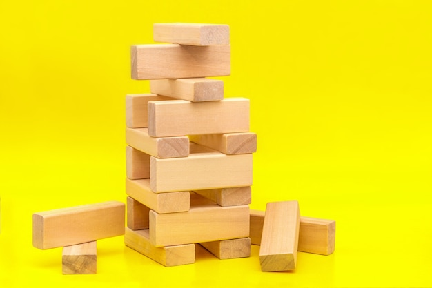 Tower of wooden blocks on yellow background with a copy of the space. concept of building business or building team.