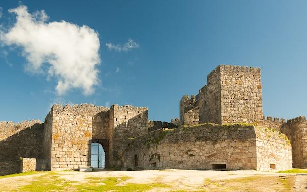 トルヒーリョのアルカサバとも呼ばれる城の曇りの日の塔と石壁のファサードはマーロンで飾られています