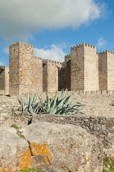 Trujillo의 alcazaba라고도 불리는 성에서 흐린 날에 merlons가있는 탑과 돌담 외관