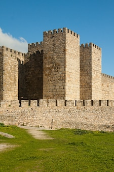 Towers and stone walls facade with merlons on a cloudy day at the castle also called alcazaba of trujillo