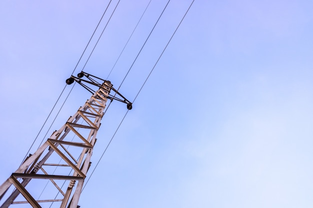 Towers with high voltage cables, against the blue sky