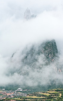 Città e una montagna rocciosa ricoperta di nebbia